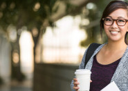 Young learner smiling holding takeaway coffee cup