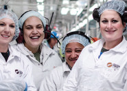 Four women smiling in protective gear in factory