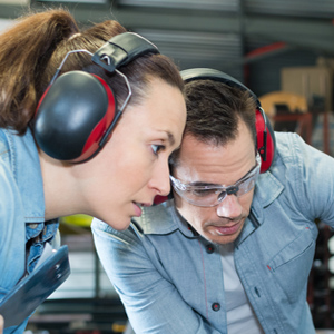 Man and woman in workshop earmuffs looking intently